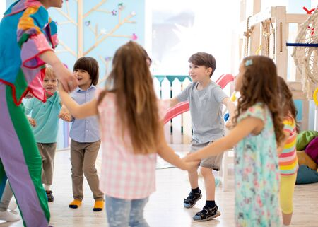 Children playing games holding hands in circle in daycare Imagens