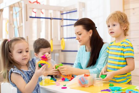 kids with play clay toys in kindergarten