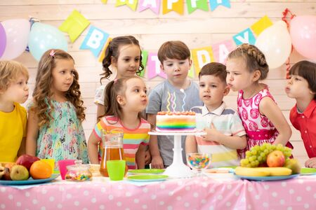 Children at table celebrating birthday holiday. Kids blows together candles on festive cake