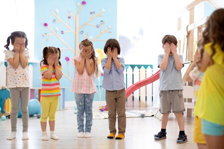 Kindergarten pupils cover their eyes at the instruction of their teacher during class activity
