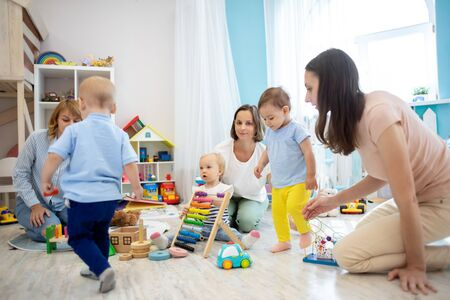 Small babies with their parents play in kindergarten