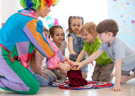 Group of happy smiling kids watching at clown show indoor. Party for children.