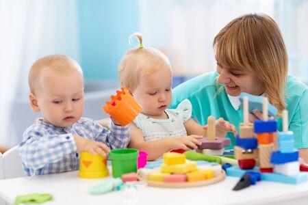 Kindergärtnerin und süße Babys, die mit Spielzeug in der Krippe spielen Standard-Bild