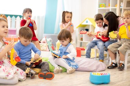 Kindergarten teacher with children on music lesson in day care. Little kids toddlers play together with developmental toys.