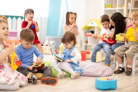 Maestra de jardín de infantes con niños en la lección de música en la guardería. Los niños pequeños juegan juntos con juguetes de desarrollo.