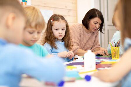 Children with teacher in classroom. Group of children doing project in kindergarten. Kids hands crafting into team.
