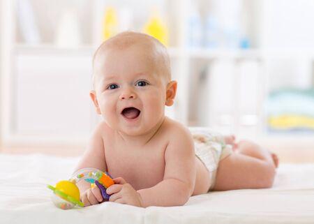 Bebé recién nacido acostado sobre el vientre pañal con mordedor