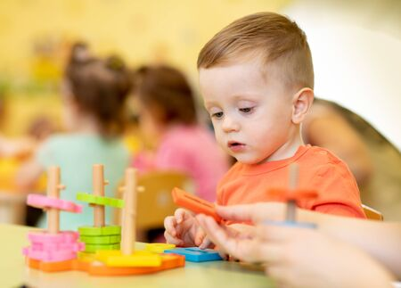 Little boy playing with educational toy in creche or nursery