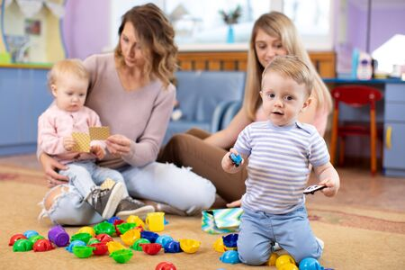 Children 1 year age playing in kindergarten or daycare centre under the supervision of moms