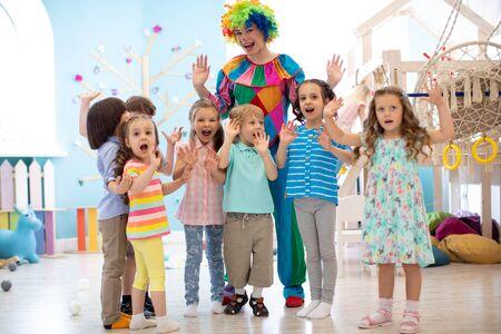 Clown et enfants jouant à l'intérieur. Vacances dans un club enfants. Jeux avec animateur Banque d'images