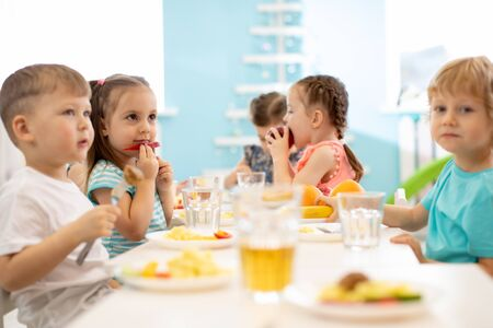 group of children eating from plates in daycare centre