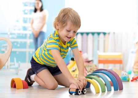kid toddler playing wooden toys in kindergarten or nursery Imagens