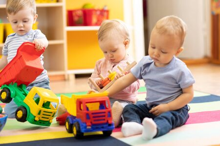 Little toddlers boys and a girl playing together in nursery or creche. Preschool children in day care centre