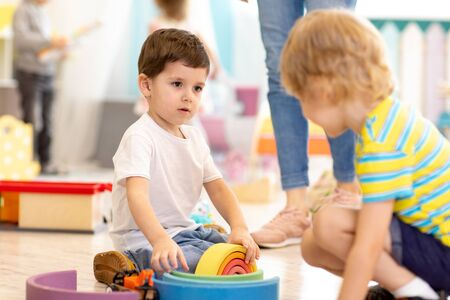 kids prescoolers playing wooden toys in kindergarten or nursery Imagens