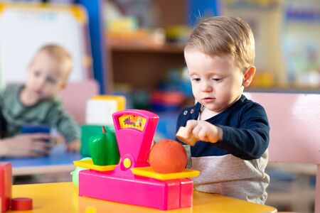 Cute little kid boy playing with abacus in nursery. Preschooler having fun with educational toy in daycare or creche. Smart child learning to count. 写真素材 - 131932910