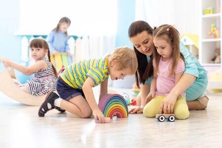 Grupo de niños jugando en el jardín de infantes. Niños con maestro en el aula.