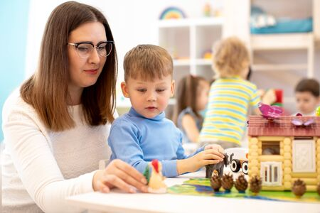 Kindergarten kid boy building toy house in play room at preschool, education concept.