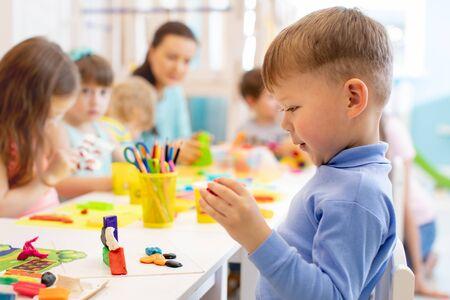 Kinderjunge und Kindergruppe, die im Kindergarten mit buntem Tonspielzeug arbeiten. Kreatives Kinderformen im Kindergarten. Vorschulkinder spielen mit Plastilin oder Teig.