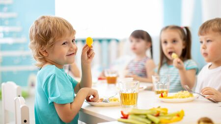 kids eating healthy food in kindergarten or daycare