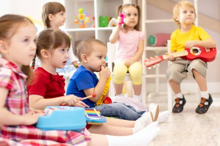 Group of preschooler children playing with musical toys at kindergarten 写真素材 - 132148190