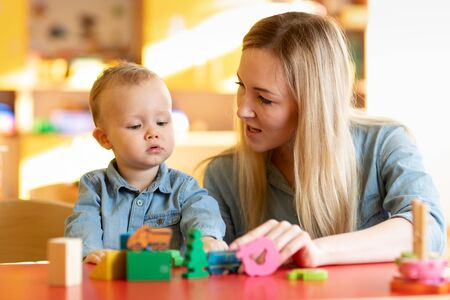 Mother and child son are talking and smiling while playing with educational toys together at home