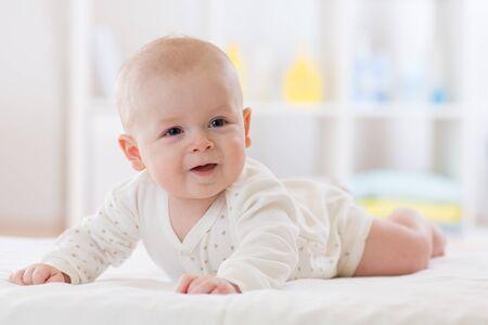Cute baby boy lying on belly in nursery room