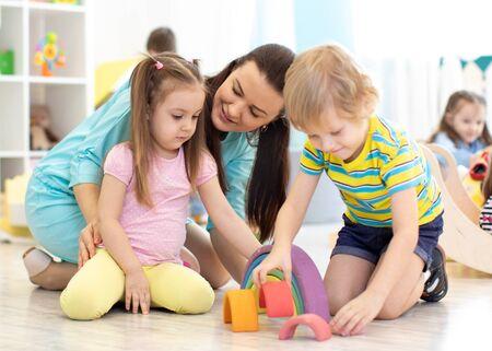 Niños en edad preescolar y maestra de jardín de infantes jugando con juguetes de madera