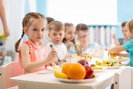 Group of kids have lunch in daycare. Children eat healthy food in kindergarten Imagens