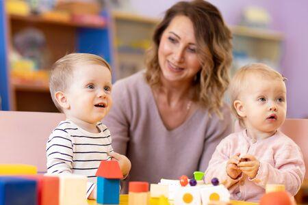 Maestra de jardín de infantes cuidando a los niños en la guardería. Los bebés de la guardería juegan juntos con juguetes de desarrollo. Foto de archivo