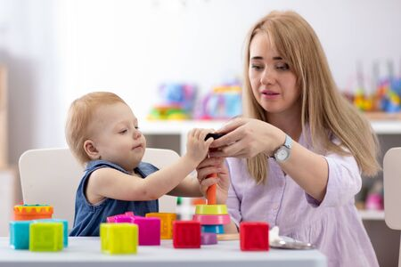 Bebé juega con niñera o mamá en la guardería o jardín de infantes
