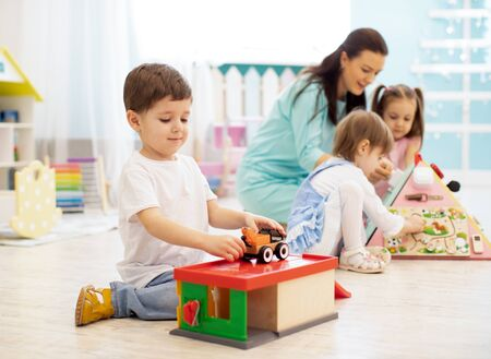 Children with teacher in daycare. Kids play with educational toys in kindergarten. Little boy playing with car and parking garage. Stockfoto