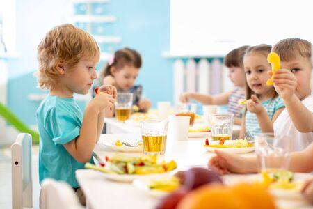 Group of children have dinner. Kids eat healthy food in kindergarten.
