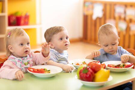Niños comiendo en jardín de infantes o guardería.