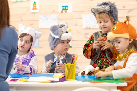 Kids with teacher make hands crafts in kindergarten. Children prepare to christmas holiday. Group of preschoolers on lesson in classroom Stockfoto