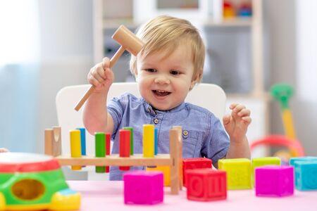 śliczny maluch bawiący się drewnianą zabawką z klockiem młotkowym