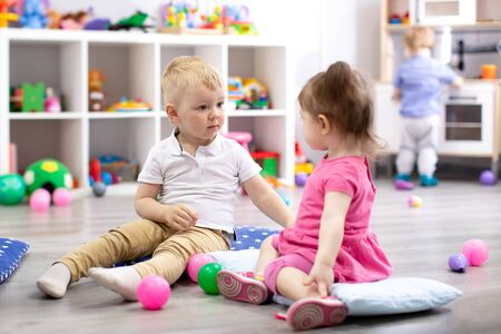Children playing with colorful toys. Little kid girl and toddler boy with educational toy blocks. Children play at day care or preschool.