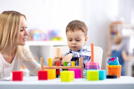 Cute toddler baby playing with wooden hammer block toy. Woman mother or teacher teaching kid in nursery