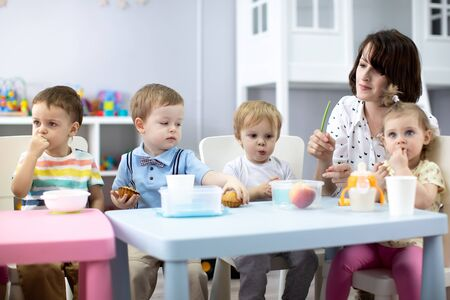 kids group have lunch with teacher in nursery Imagens