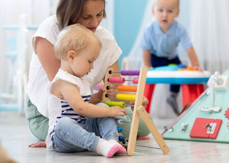 Kids playing on floor with educational toys in kindergarten. Children have fun in nursery or daycare. Babies with teacher in creche