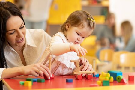 Little caucasian girl playing with Montessori toy in pre-school. Woman teaching kid in kindergarten Imagens