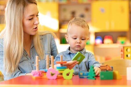 Nursery baby and carer play at table in daycare centre Imagens
