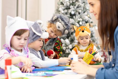 Group of preschoolers weared funny clothes on lesson in classroom. Kids with teacher make hands crafts in kindergarten. Children prepare to christmas holiday. Imagens