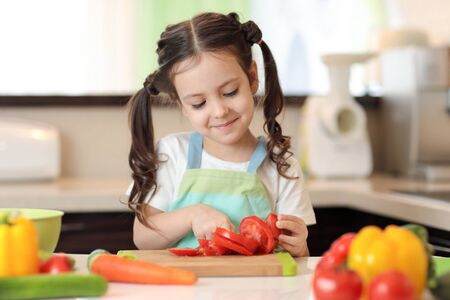 happy kid girl chopping tomatoes on cutting board with knife in kitchen Imagens