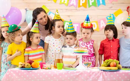 Group of adorable kids gathered around festive table. Birthday party for preschoolers