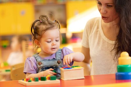 Parent and little kid playing with educational toys, stacking and arranging colorful pieces. Imagens