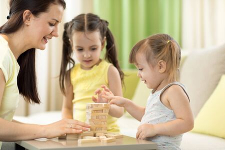 Mother with kids play jenga game in living room