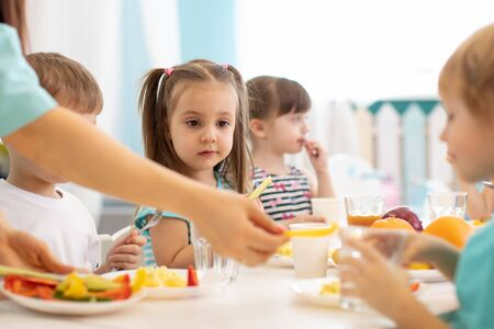 Kids have a dinner in preschool. Little boys and girls from the group of children sit at table with lunch and eat appetizing. Children with caregiver in day care centre
