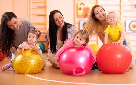 Group of young mothers and their kids doing yoga exercises on gymnastic balls at fitness gym Imagens