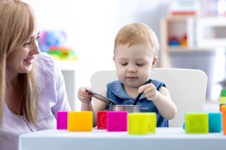Baby with mom play in nursery Imagens