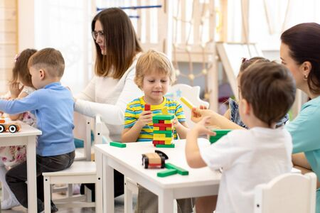 Children group and teacher playing with building blocks together in preschool